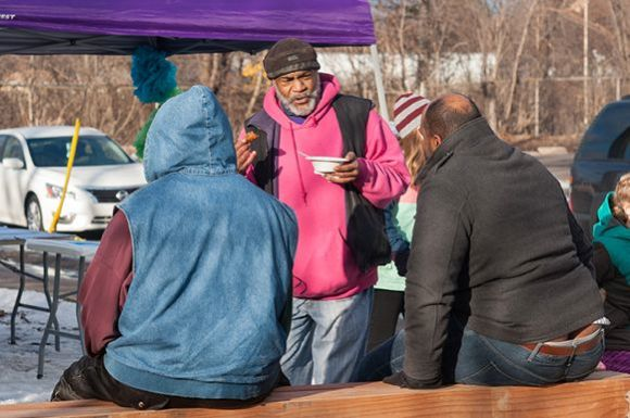 Melvin Giles, an organizer with Friendly Streets, greets Rondo neighbors